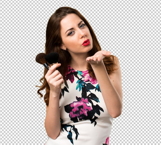 Linda garota com pincel de maquiagem mandando um beijo