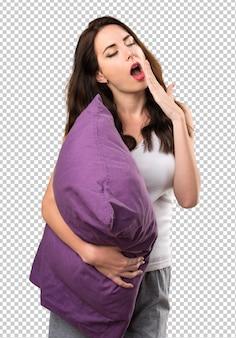 Linda garota com um travesseiro bocejando