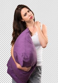 Linda garota com um travesseiro com dor no ombro