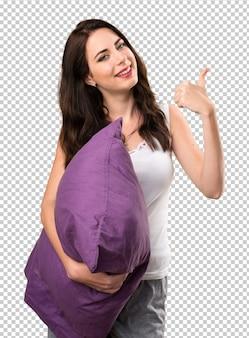 Linda garota com um travesseiro com o polegar para cima