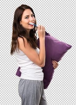 Linda garota com um travesseiro e com uma escova de dentes