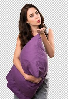 Linda garota com um travesseiro enviando um beijo