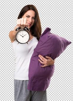 Linda garota com um travesseiro segurando o relógio vintage