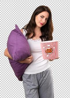Linda garota com um travesseiro segurando pipocas