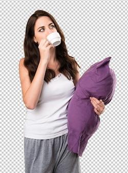 Linda garota com um travesseiro segurando uma xícara de café
