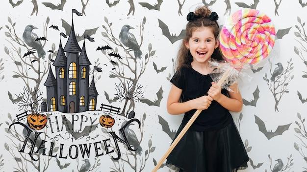 Linda garota segurando um evento de halloween pirulito gigante