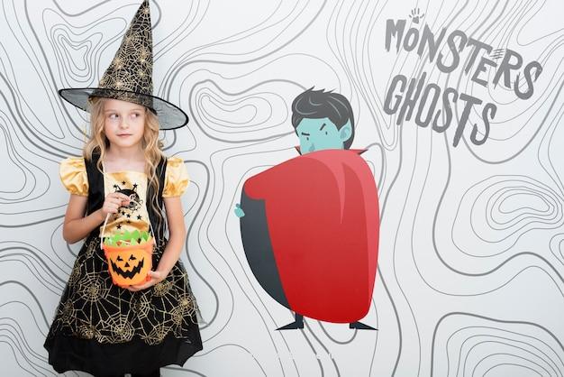 Linda garota vestida como uma bruxa em pé nas proximidades de um vampiro animado