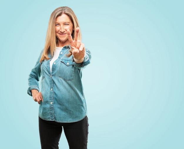 Linda mulher sênior com uma expressão orgulhosa, feliz e confiante; sorrindo e mostrando o sucesso