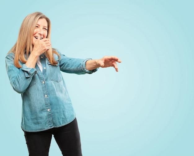 Linda mulher sênior rindo duro em algo hilário e apontando para os lados