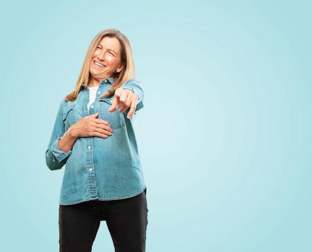 Linda mulher sênior rindo muito de algo hilário e apontando para você