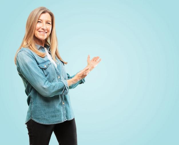Linda mulher sênior sorrindo com um olhar orgulhoso, satisfeito e feliz, acolhendo o gesto ou mostrando