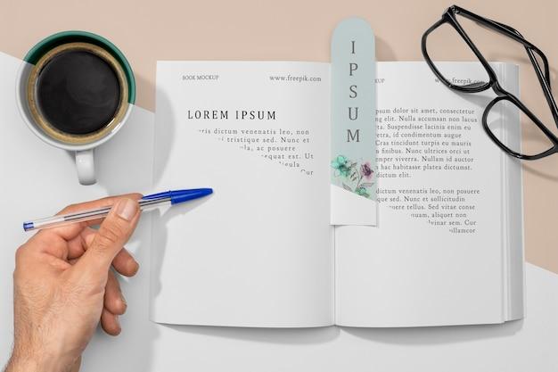 Livro aberto plano e modelo de marcador com café