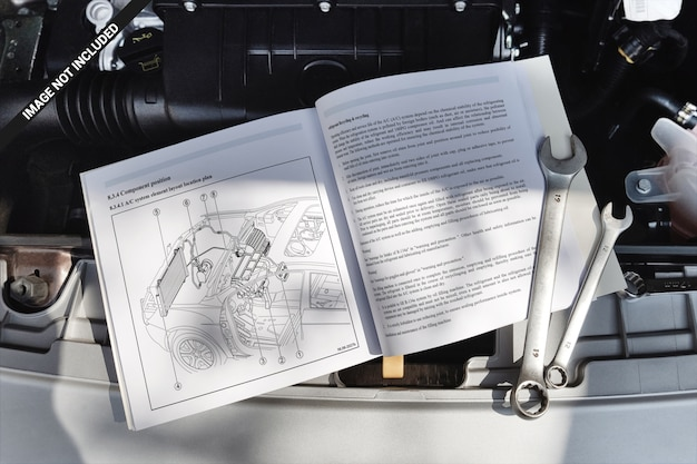 Livro de capa mole aberto, deitado sobre uma maquete de motor de carro