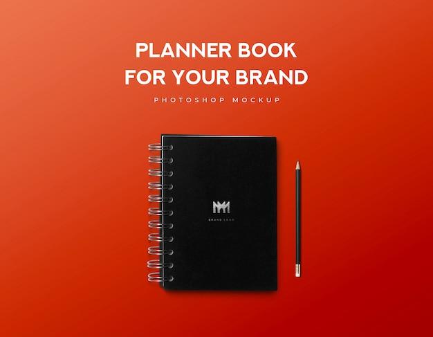 Livro de planejador para sua marca e lápis preto sobre fundo vermelho