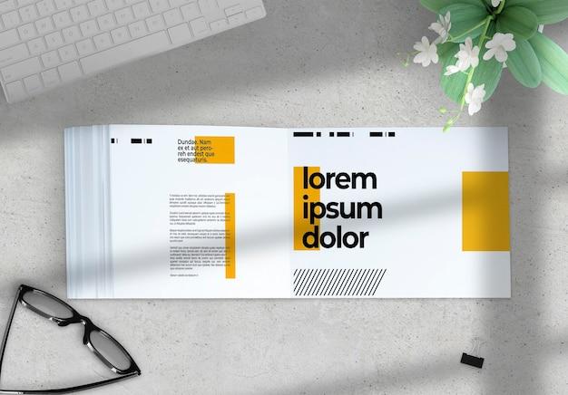 Livro horizontal aberto em uma maquete de desktop com elementos deco