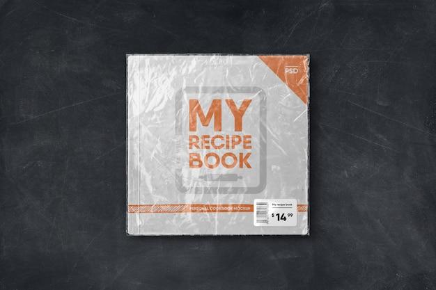 Livro quadrado de capa mole em embalagem plástica com maquete de etiqueta de preço