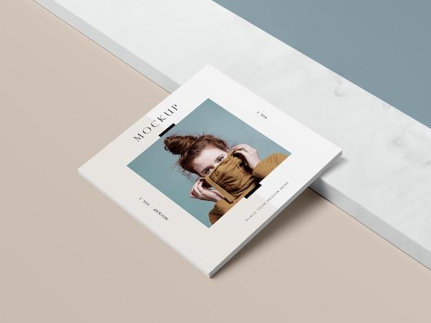 Livro quadrado de vista alta com maquete de revista editorial de mulher e sombra