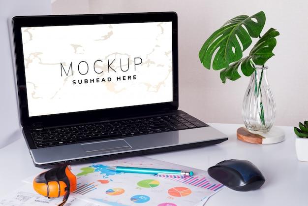 Local de trabalho com folhas de laptop, desenho e monstera