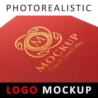 Logo maquete - logotipo dourado impresso na capa de tecido vermelho