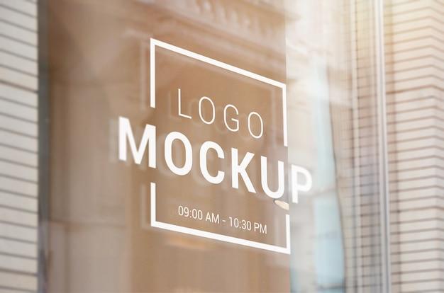 Logotipo, assinar maquete na janela de vidro da loja. apresentação da marca do logotipo