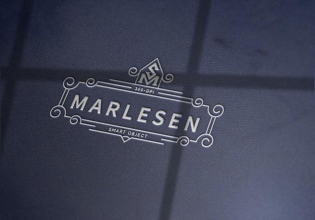 Logotipo elegante em textura de tecido com maquete de efeito gravado