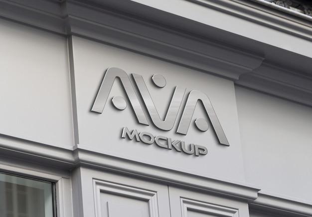 Logotipo metálico em uma fachada de loja na rua mockup