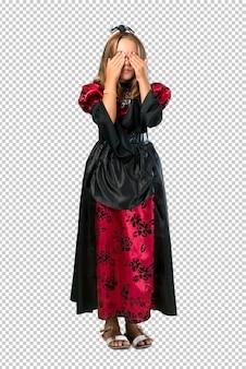 Loira criança vestida como um vampiro para as férias de halloween cobrindo os olhos pelas mãos