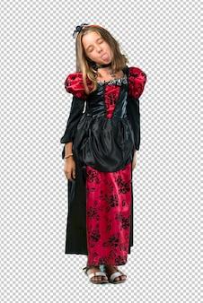 Loira criança vestida como um vampiro para as férias de halloween mostrando a língua para a câmera