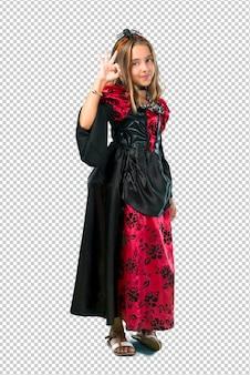 Loira criança vestida como um vampiro para as férias de halloween, mostrando um sinal de ok com os dedos