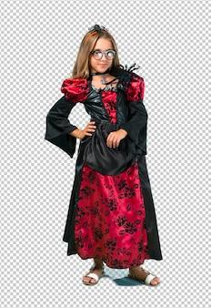 Loira criança vestida como um vampiro para as férias de halloween, posando com os braços no quadril