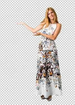 Loira jovem em um vestido de verão apresentando e convidando para vir