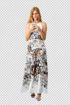 Loira jovem em um vestido de verão, enviando uma mensagem ou e-mail com o celular