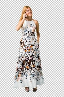 Loira jovem em um vestido de verão, mantendo uma conversa com o celular com alguém
