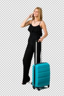Loira viajando com sua mala, mantendo uma conversa com o celular com alguém