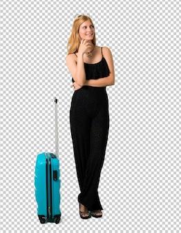 Loira viajando com sua mala sorrindo muito enquanto coloca as mãos no peito