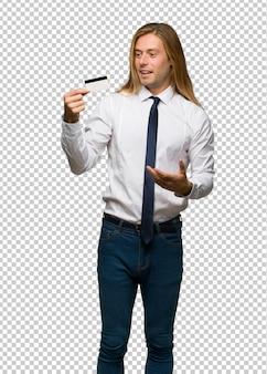 Loiro empresário com cabelo comprido, segurando um cartão de crédito e surpreso