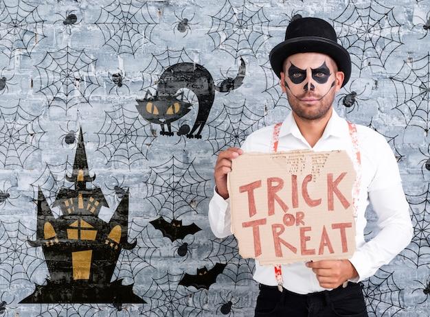 Macho com maquiagem, segurando um cartão com letras doces ou travessuras para o halloween