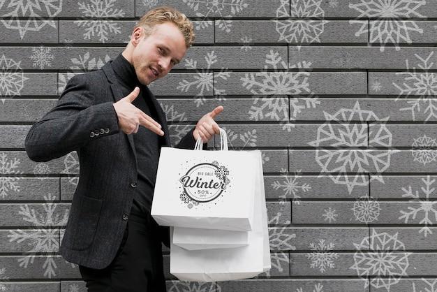 Macho feliz, apontando para seus sacos de compras