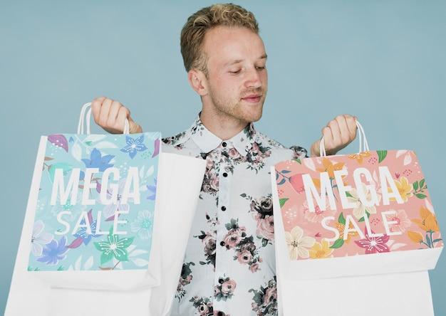 Macho novo que verifica sacos de compras