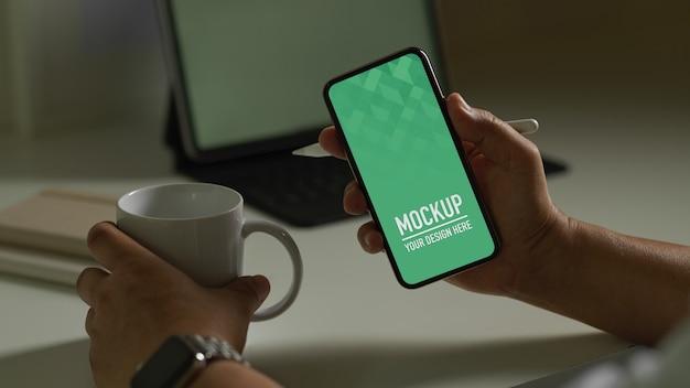 Macho segurando maquete de smartphone e xícara de café