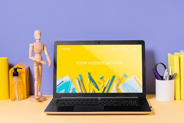 Manequim de madeira e laptop com maquete
