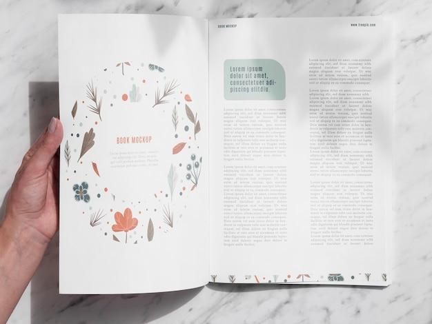 Mão abrindo uma revista em fundo cinza