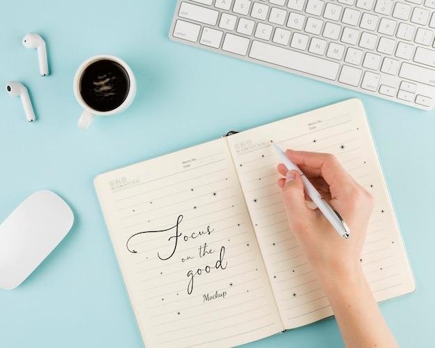 Mão de close-up com caneta e caderno