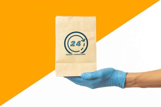 Mão de homem entrega segurando modelo de maquete de saco de papel de comida