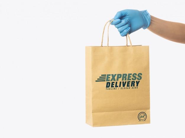 Mão de homem entrega segurando modelo de maquete de sacola de papel ofício, maquete de embalagens, conceito de serviço de entrega
