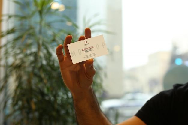 Mão de homem segurando a maquete do cartão psd