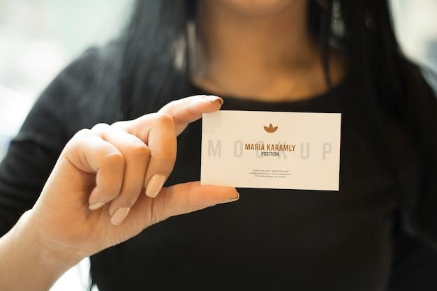 Mão de menina feminina segurando maquete de cartão de visita psd