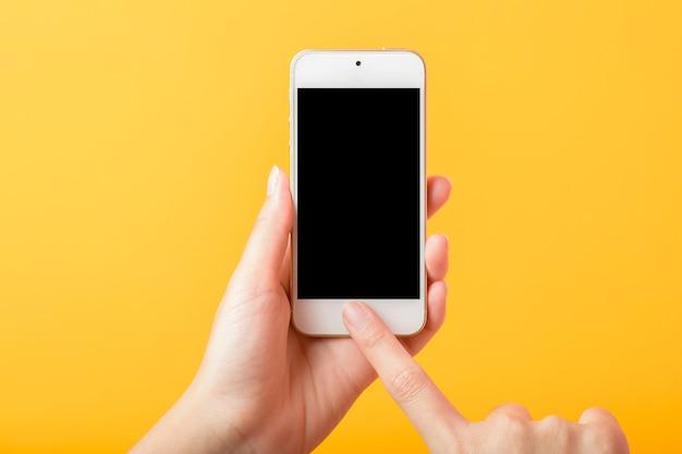 Mão de mulher está segurando maquete de telefone inteligente em fundo amarelo
