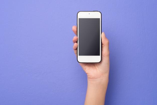 Mão de mulher está segurando maquete de telefone no fundo roxo