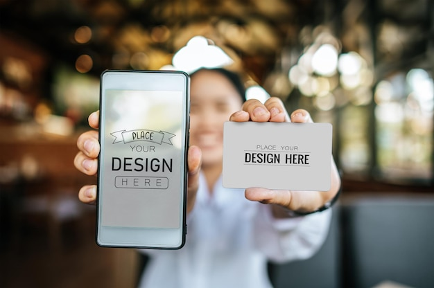 Mão de mulher segura maquete de smartphone e cartão de crédito psd